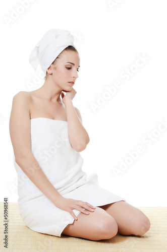 The beautiful woman in a towel on bamboo rug. SPA concept.