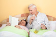 Funny seniors relax with alcohol in bed