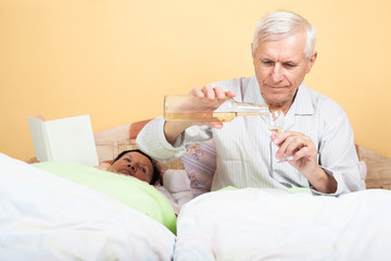 Seniors man with alcohol in bed