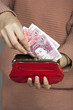 Woman's hand and fifty pound notes in a purse