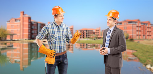 Manual worker having a conversation with architect, buildings in
