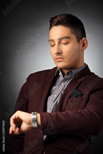 Handsome fashionable guy checking the time on his watch