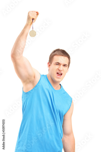Young euphoric sportsman holding a gold medal