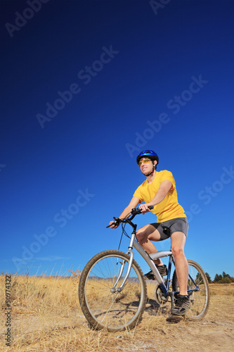 A young male with yellow shirt and helmet riding a mountain bike