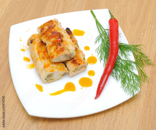 stuffed chicken rolls, chili and dill twig on a white plate