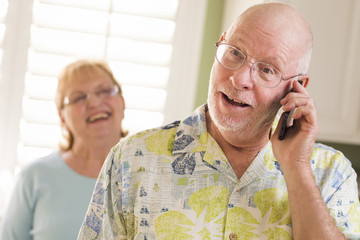 Senior Adult Husband on Cell Phone with Wife Behind
