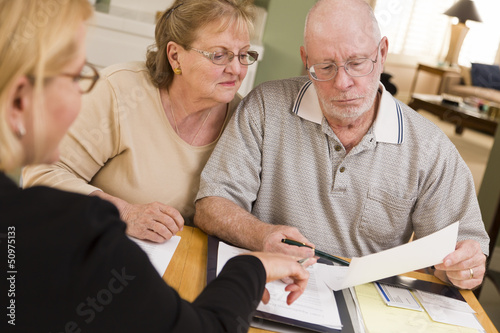 Leinwandbild Motiv Senior Adult Couple Going Over Papers in Their Home with Agent