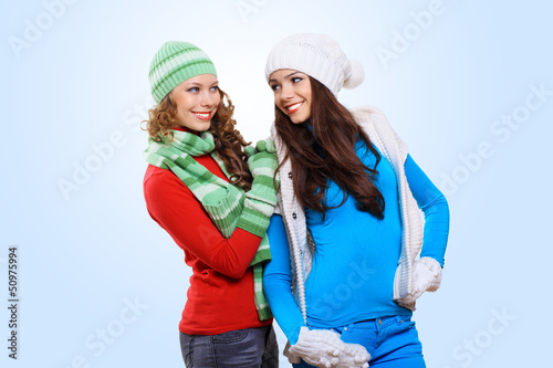 Two girls in winter hats and scarfs