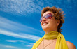 Smiling woman in sunglasses and yellow scarf admiring sea views