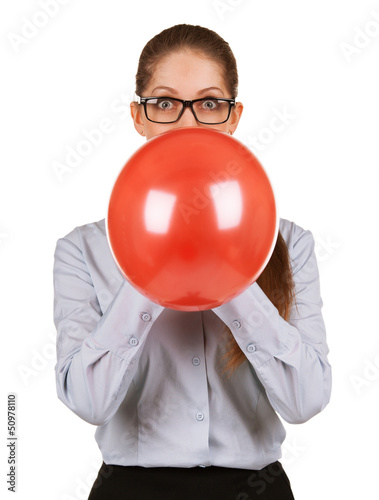 Girl inflating a large red balloon