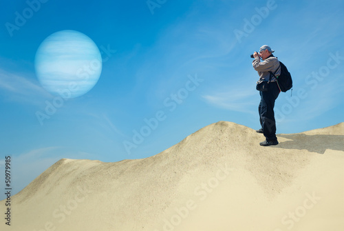 Tourist on a desolate planet taking photograph of its satellite