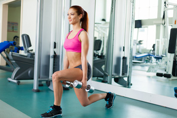 fitness model works out with dumbbells in fitness center