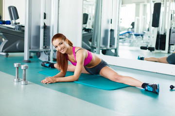 Attractive young fitness model exercising in the gym