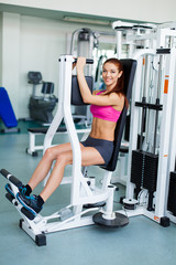 fitness model works out on training apparatus in fitness center