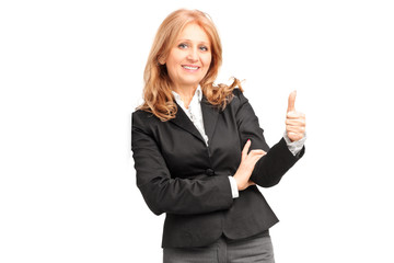 A smiling businesswoman leaning on wall and giving a thumb up