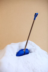 blue snow shovel standing up in deep snow