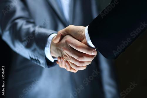 Leinwanddruck Bild Handshake - Hand holding on black background