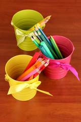 Colorful pencils and felt-tip pens in color pails close-up