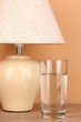 table lamp and glass of water on beige background