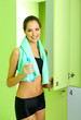 Young girl in locker room with towel and bottle of water