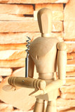 Mannequin with corkscrew, on brown wall background