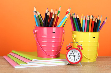 Colorful pencils in two pails with copybooks