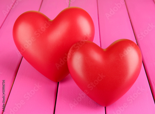 Decorative red hearts on color wooden background