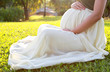 Beautiful pregnant woman relaxing in the park at the morning