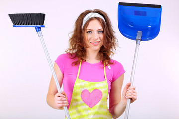 Young housewife with broom and dustpan on grey background