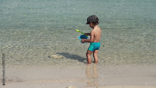 Cute kid playing in the sea, super slow motion