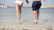Young couple running to the sea, super slow motion