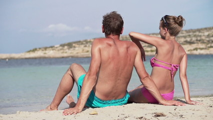 Young couple sitting on the beach, super slow motion