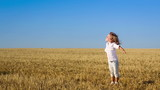 Happy child enjoying the sun in summer field. Slow motion