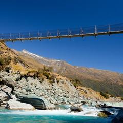 Swing bridge high over glacial river New Zealand