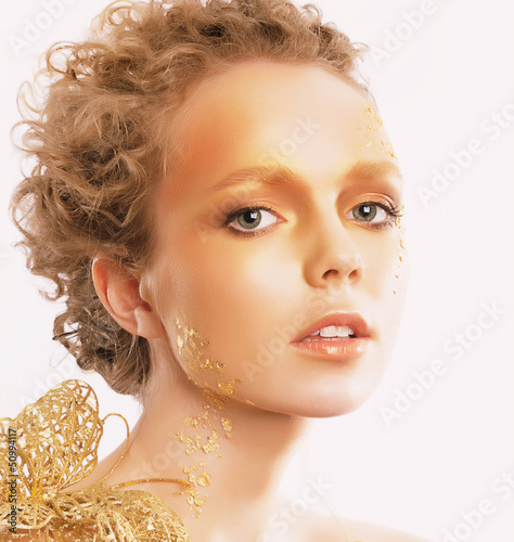 Golden Woman's Face. Curly Hair. Professional Bronzed Makeup