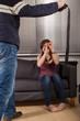 Der Mann bedroht seine Freundin mit einem Gürtel