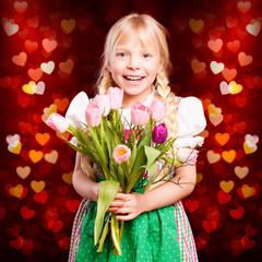 junges Mädchen mit Tulpenstrauß vor Herzenhintergrund