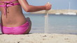 Sexy woman sitting on the beach, super slow motion