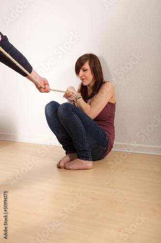 Das junge Mädchen ist an den Händen gefesselt