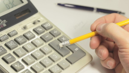 Accounting. Man working with a calculator. Close up.