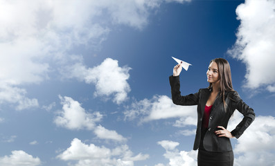 Business woman throwing a paper plane