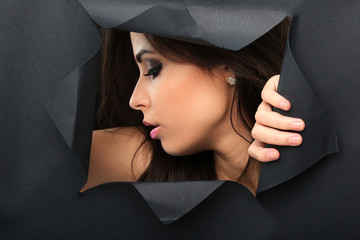 Beautiful girl with face framed in a black sheet