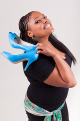 Beautiful  African American woman holding  a pair of shoes