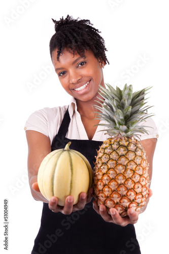 Young happy black / african american woman selling fresh fruits