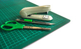 A pair of scissors , cutter and stapler  on  cutting mat