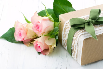Gift box wrapped in brown paper, white lace and a green bow