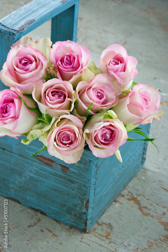 Roses in an old blue wooden gardening basket