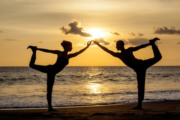 Couple doing exercise yoga together stretching while sunset