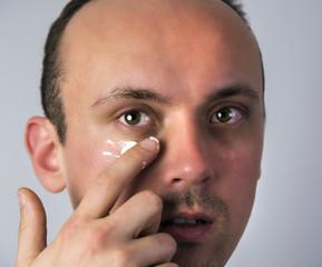 Mann cremt sich das Gesicht ein