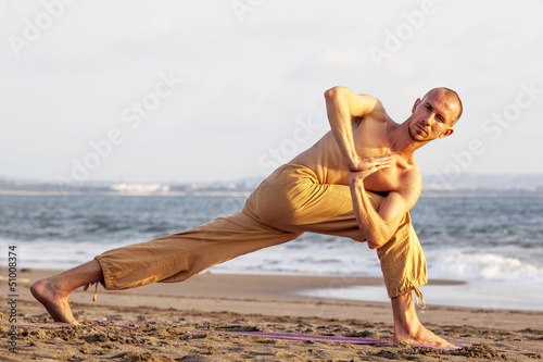 Bare-chested man practicing yoga on mat at beach
